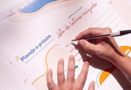 Duas mãos brancas escrevem com caneta sobre planejamento impresso